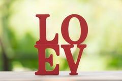 Les lettres en bois expriment le ` d'AMOUR de ` avec la lettre en bois L, O, V et E sur la table en bois Photographie stock libre de droits