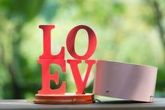 Les lettres en bois expriment le ` d'AMOUR de ` avec la lettre en bois L, O, V et E sur la table en bois Image stock