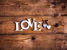 Les lettres en bois formant le mot AIMENT écrit sur le fond en bois Jour du ` s de St Valentine deux coeurs et Photographie stock libre de droits