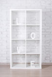 Les lettres en bois formant le mot AIMENT dans l'étagère moderne au-dessus de bric blanc Image stock