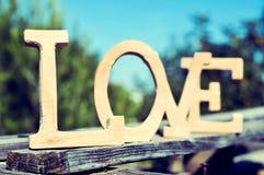 Les lettres en bois formant le mot aiment dans un paysage rustique Photos libres de droits