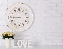 Les lettres en bois formant le mot AIMENT, les fleurs et l'horloge de vintage plus de Image libre de droits