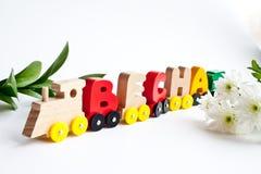 Les lettres en bois russes forment le ressort de mot couleurs jaunes rouges en bois sur un blanc Éducation de petite enfance, app photographie stock