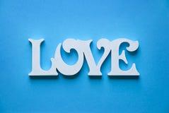 Les lettres formant le mot AIMENT écrit sur le fond bleu de papier Photographie stock libre de droits