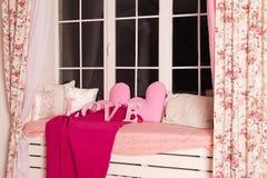 Les lettres roses décoratives formant le mot AIMENT avec les oreillers roses Photo stock