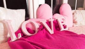 Les lettres roses décoratives formant le mot AIMENT avec les oreillers roses Image stock