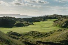 Les liens jouent au golf le trou avec de grandes dunes de sable et l'océan à l'arrière-plan Image libre de droits
