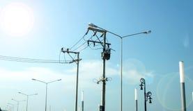 Les lignes à haute tension s'approchent de la lumière de lampe et de soleil Photo stock