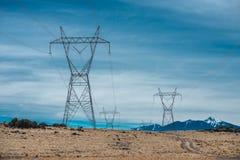 Les lignes électriques à haute tension en montagne abandonnent contre le ciel bleu Images libres de droits