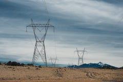 Les lignes électriques à haute tension en montagne abandonnent contre le ciel bleu Photographie stock