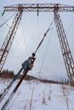 Les lignes électriques de transmission de l'électricité sur la haute tension de fond d'hiver dominent Image stock