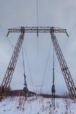 Les lignes électriques de transmission de l'électricité sur la haute tension de fond d'hiver dominent Photos stock