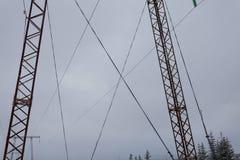 Les lignes électriques de transmission de l'électricité sur la haute tension de fond d'hiver dominent Photo libre de droits