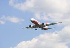 Les lignes aériennes d'ailes de rouge de l'avion TU-204-100B RA-64043 vient sur l'atterrissage Photo libre de droits