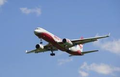 Les lignes aériennes d'ailes de rouge de l'avion TU-204-100B RA-64043 vient sur l'atterrissage Images libres de droits