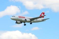 Les lignes aériennes internationales suisses de l'avion HB-IPY d'Airbus A319-112 volant dans le ciel nuageux Images libres de droits