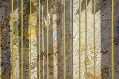 Les lignes jaunes verticales contre un brun gris blanc tache le granit avec des ombres Texture de surface approximative image libre de droits