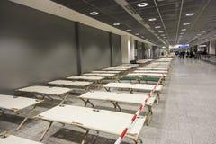Les lits de camp vides tiennent la rangée à côté de rangée dans le terminal d'aéroport Photo libre de droits