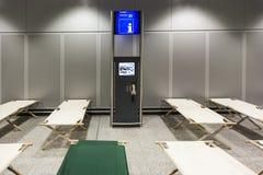 Les lits de camp vides tiennent la rangée à côté de rangée dans le terminal d'aéroport Photos stock