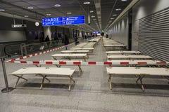Les lits de camp vides tiennent la rangée à côté de rangée dans le terminal d'aéroport Images libres de droits