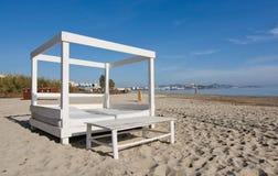 Les lits pliants blancs sur le Playa arénacé d'en la plage de Bossa Photo stock