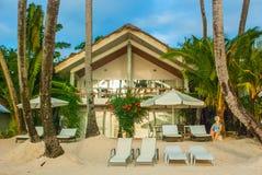 Les lits pliants du ` s d'hôtel avec des parasols sur la plage Boracay, Philippines photographie stock libre de droits