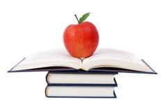 Les livres dominent avec la pomme d'isolement sur le blanc photos libres de droits