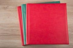 Les livres en cuir rouges et bleus s'étendent sur le fond en bois Image libre de droits