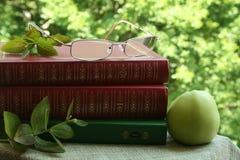 Les livres et les lunettes et la pomme verte Photo stock