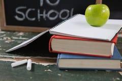 Les livres, la pomme et l'ardoise embarquent avec de nouveau au texte d'école Photo libre de droits