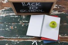 Les livres, la pomme et l'ardoise embarquent avec de nouveau au texte d'école Image libre de droits