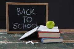 Les livres, la pomme et l'ardoise embarquent avec de nouveau au texte d'école Photos libres de droits