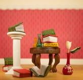 Les livres miniatures et les vases sur la table avec se sont levés Photos stock