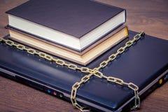 Les livres se trouvent sur un ordinateur portable qui est attaché avec une chaîne Amour au read_ photos libres de droits