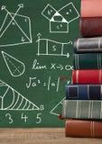 Les livres sur le bureau avec des graphiques de tableau noir des maths diagrams Photos libres de droits