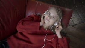 Les loisirs de personnes détendent le concept Jeune femme dans la musique de écoute d'écouteurs et détente à la maison sur le sof clips vidéos