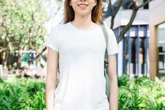 Les longs cheveux bruns de fille asiatique de hippie dans le T-shirt vide blanc se tiennent au milieu de la rue images stock