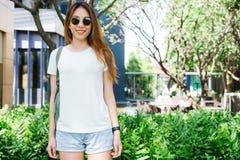 Les longs cheveux bruns de fille asiatique de hippie dans le T-shirt vide blanc se tiennent au milieu de la rue photographie stock libre de droits