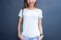 Les longs cheveux bruns de fille asiatique de hippie dans le T-shirt vide blanc se tiennent au milieu de la rue photos stock
