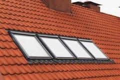 Les lucarnes de toit ont couvert de tuiles le toit Photo stock
