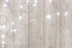Les lumières de Noël blanc acculent la frontière au-dessus du bois gris-clair image libre de droits