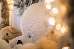 Les lumières de Noël brouillent et les ours de nounours blancs étend d'intérieur avec le cône de pin à l'arrière-plan Assaisonne  Photographie stock libre de droits