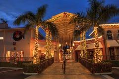 Les lumières de Noël rougeoient au coucher du soleil au-dessus des magasins colorés du V image stock