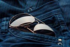 Les lunettes de soleil d'aviateur dans des jeans empochent photographie stock