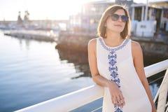 Les lunettes de soleil de port et l'été de femme s'habillent à côté de l'eau Photographie stock