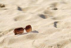 Les lunettes de soleil des femmes sur le sable. Image libre de droits