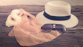 Les lunettes de soleil et le comprimé élégants de femme de chapeau façonnent l'écharpe au-dessus du woode photos libres de droits