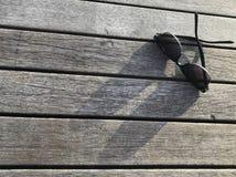 Les lunettes de soleil et son ombre brillent sur le banc en bois Images libres de droits