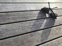 Les lunettes de soleil et son ombre brillent sur le banc en bois de couleur naturelle Photos libres de droits