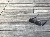Les lunettes de soleil ont mis dessus le banc en bois de couleur naturelle dans la lumière de jour Images stock